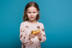 Pretty, little girl in sweater with brunet hair hold a burger. Isolated on blue, attractive caucasian brunette child with long hair, in beige coat and blue jeans Royalty Free Stock Photography