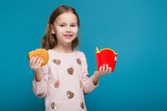 Pretty, little girl in sweater with brunet hair hold a burger. Isolated on blue, attractive caucasian brunette child with long hair, in beige coat and blue jeans Royalty Free Stock Image