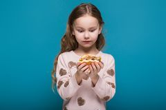 Pretty, little girl in sweater with brunet hair hold a burger. Isolated on blue, attractive caucasian brunette child with long hair, in beige coat and blue jeans Royalty Free Stock Photo