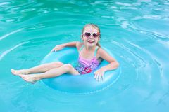 Free Pretty Little Girl Swimming In Outdoor Pool And Have A Fun With Inflatable Circle Stock Image - 155894881