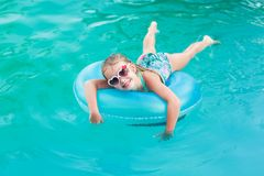 Free Pretty Little Girl Swimming In Outdoor Pool And Have A Fun With Inflatable Circle Royalty Free Stock Image - 155894966