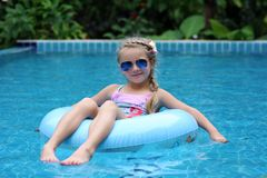 Free Pretty Little Girl Swimming In Outdoor Pool And Have A Fun With Inflatable Circle Stock Photography - 155894992