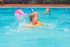 Pretty little girl swimming in outdoor pool and have a fun with inflatable circle stock photography