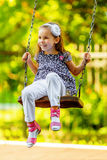 Pretty little girl swinging on seesaw Stock Image