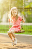 Pretty little girl swinging on seesaw under bright shining Royalty Free Stock Photography