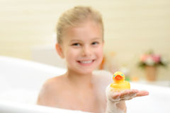 Pretty little girl taking bath. We are best friends. Pleasant smiling little girl sitting in the bath tube and holding rubber duck while taking bath stock photo