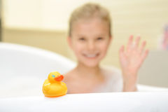 Pretty little girl taking bath. My best toy. Cute little yellow rubber duck standing on the bath tube with little girl taking bath in the background stock photography