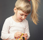 Pretty little girl threading beads on an yellow wire Royalty Free Stock Photo