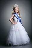 Pretty little girl in tiara and long white dress Stock Photos