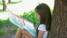 Pretty little girl tired after drawing with gouache sitting near the tree in the park. Close up stock video footage