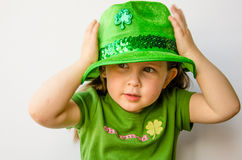 Pretty little girl tries on hat. Closeup of a pretty little girl with brunette hair tries on a green hat to celebrate St. Patrick's Day  on a white background Stock Photos