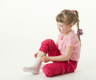 Pretty little girl trying on sock Royalty Free Stock Photos