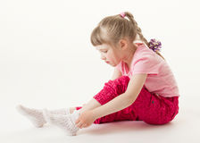 Pretty little girl trying on sock Stock Images