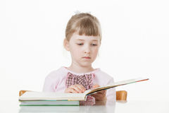 Pretty little girl turning over pages of a book Royalty Free Stock Images