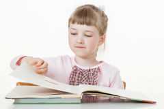 Pretty little girl turning over pages of a book Royalty Free Stock Image