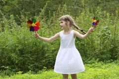 Pretty little girl with two windmills spins Royalty Free Stock Photos