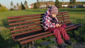 Pretty little girl using app on smartphone sits on bench in the park. stock footage