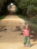 Pretty little girl walking. A young pretty blond girl walking towards the camera down a country path in the shade Stock Photo