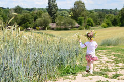 Pretty little girl walking away on rural road Royalty Free Stock Photography