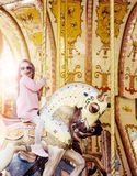 Pretty little girl, wearin sunglusses, riding the horse of merry-go-round. stock photos