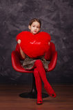 Pretty little girl wearing beautiful dress sitting in red armchair. She is holding plush heart in hands. Studio shot. Pretty little girl wearing beautiful dress Stock Image