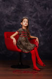 Pretty little girl wearing beautiful dress sitting in red armchair. She is wearing red masquerade carnival mask. Studio shot. Royalty Free Stock Photography