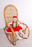 Pretty little girl wearing Christmas dress. Sitting on wooden rocking chair Stock Images