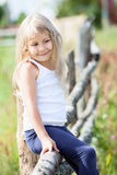 Pretty little girl in white singlet sitting on fence Stock Images