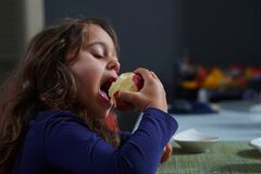 Free Pretty Little Girl With Big Eyes Eats A Red Apple Stock Image - 176955471