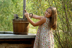 Pretty little girl with wooden bucket Stock Photos