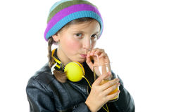 A pretty little girl with a woolen cap drinking a glass of orang Stock Photos