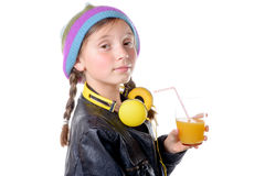 A pretty little girl with a woolen cap drinking a glass of orang Stock Images