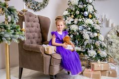 Pretty little girl 4 years old in a blue dress. Baby in Christmas room with teddybear, big clock, christmas tree, brown armchair, stock photo