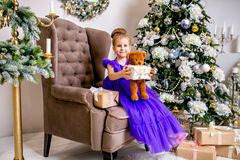 Pretty little girl 4 years old in a blue dress. Baby in Christmas room with teddybear, big clock, christmas tree, brown armchair, royalty free stock images