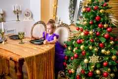 Pretty little girl 4 years old in a blue dress. The child at the table before the Christmas dinner royalty free stock images