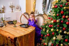 Pretty little girl 4 years old in a blue dress. The child at the table before the Christmas dinner stock image