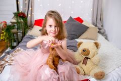 Pretty little girl 4 years old in a pink dress. Child in the Christmas room with a bed, eating candy, chocolate, cookies and drink royalty free stock photo