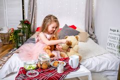 Pretty little girl 4 years old in a pink dress. Child in the Christmas room with a bed, eating candy, chocolate, cookies and drink royalty free stock image