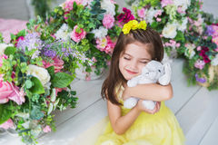 A pretty little girl in a yellow dress sits and hugs a rabbit toy in a studio Stock Photo