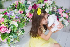 A pretty little girl in a yellow dress sits and kisses with a rabbit toy in a studio Stock Photos