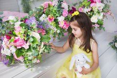A pretty little girl in a yellow dress sits and touches a flowers in a studio Stock Images