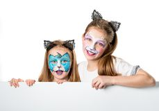 Little girls with face arts holding a sheet for your adverisement or text isolated. Pretty little girls with colourful face arts holding a sheet for your royalty free stock images