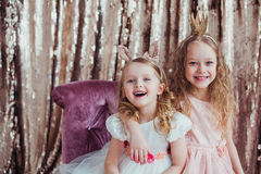 Pretty little girls. Posing against the golden background. Fashion photo. Christmas, birthday, party time Royalty Free Stock Photography