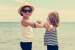 Pretty little girls (sisters) dancing on the beach. Stock Photo