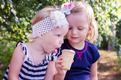 Pretty little girls (sisters) eating ice cream in the summer the Stock Photography