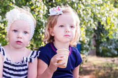 Pretty little girls (sisters) eating ice cream in the summer the Royalty Free Stock Photo