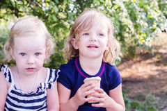 Pretty little girls (sisters) eating ice cream in the summer the Royalty Free Stock Photography