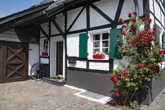 Small half-timber house with flowering red climbing roses and green window shutters Stock Photography