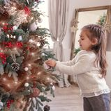 Pretty little girl decorating the Christmas tree. Pretty little happy girl decorating the Christmas tree. preparation for Christmas holiday stock images