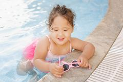 Kazakh little girl playing near swimming pool. Pretty little kazakh curly girl playing by the swimming pool Royalty Free Stock Photo